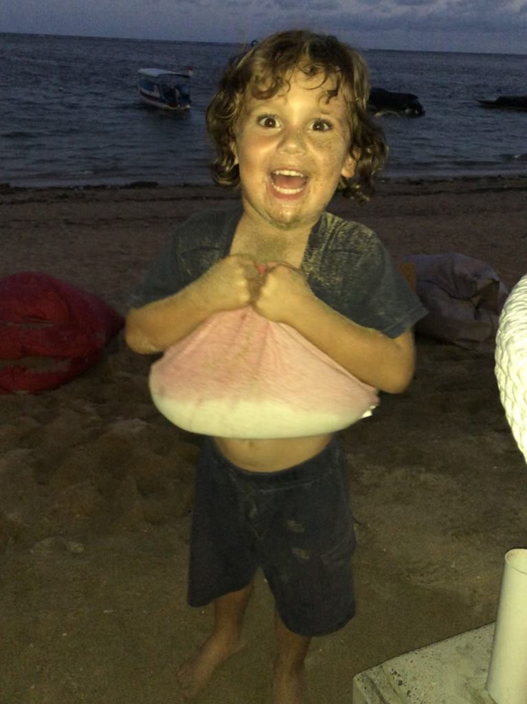 Sawyer uses his shirt to hold a bunch of sand, on cloud 9